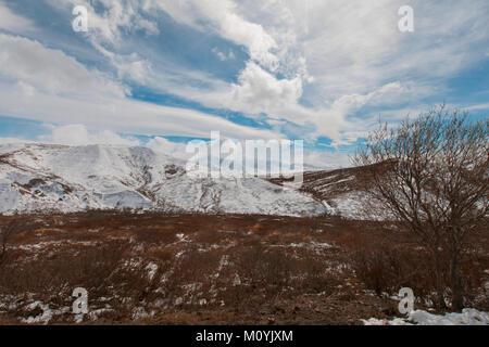 Wolken über Schnee auf dem Berg Stockbild