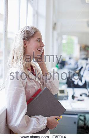 Lächelnde Geschäftsfrau hält Ordner und reden über Handy im Büro Stockbild