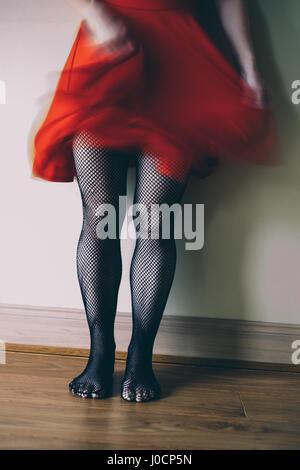 Frau im roten Kleid und Netzstrümpfe tignts Stockbild
