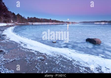 Aufgehenden Mond an einem kalten Winterabend am Oslofjord, im Ofen in Råde, Østfold Norwegen. Stockbild