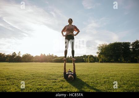 Im Freien Schuss junges Paar beim akrobatischen Yoga üben im Park. Frau auf die Füße des Menschen Stockbild