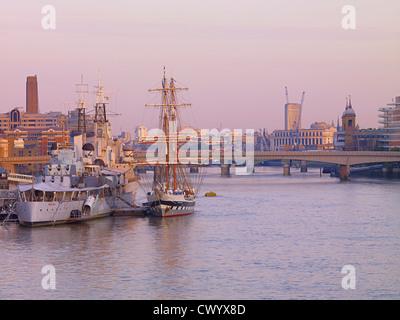 HMS Belfast mit einem Großsegler vertäut neben in der Morgendämmerung, London UK Stockbild