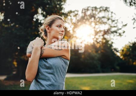Porträt von Fit junge Frau streckte Arme. Kaukasische weiblich Ausübung Morgen im Park. Stockbild