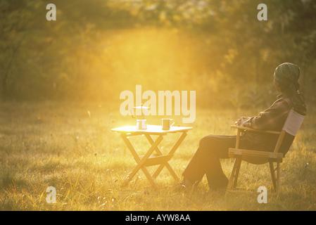 Mann mit heißem Kaffee sitzend auf einem Stuhl im Garten Stockbild