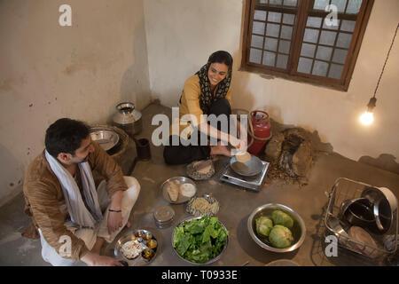 Lächelnd ländliche Frau sitzt in der Küche kochen auf einem kleinen Gaskocher mit Utensilien und Gemüse auf dem Boden, während ihr Ehemann sitzen Stockbild