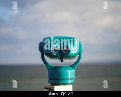 Nahaufnahme des blauen Münz-Fernglas gegen Meer an sonnigen Tag Stockbild