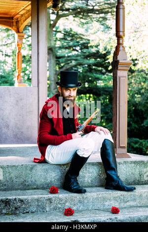 Regency Mann halten eine Pistole mit roten Rosen Stockbild