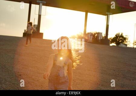 Kinder in der Tankstelle bei Sonnenuntergang Stockbild