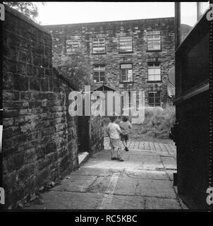 Holker Street Mühle, Burnley Straße, Colne, Pendle, Lancashire, 1966-1974. Holker Street Mühle aus der Spur läuft zwischen 48 Burnley Straße und Bethel, Kirche, mit zwei Kindern, die in der Gasse gesehen. Stockbild