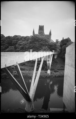 Kingsgate Brücke und Durham Cathedral, County Durham, c 1963 - c 1980. Einen allgemeinen Überblick über das Kingsgate Brücke, vom Ostufer des Flusses gesehen Tragen, und nach Westen, zeigt die volle Länge der Brücke und einen teilweisen Blick auf den Dom im Hintergrund. Die Fußgängerbrücke wurde 1963 mit Stahlbeton, mit weißem Zement und Shap Granit gebaut. Die Brücke hat zwei Längen trat in der Nähe der West Bank des Flusses, und zwei große V-förmige Pfeiler über den Fluss den Weg zu unterstützen. Im Hintergrund ist ein Teil der Osten der Erhöhung von der Kathedrale, einem ehemaligen Benediktinerkloster Pr Stockbild