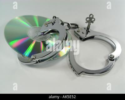 CD-Rom mit Handschellen als Symbol für Kopierschutz und oder Verhaftung nach illegale Internet-Downloads Stockbild