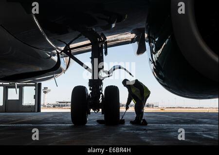 Mann arbeitet auf dem Fahrgestell eines Flugzeugs, Flughafen Berlin Brandenburg International BBI, Berlin, Deutschland Stockbild