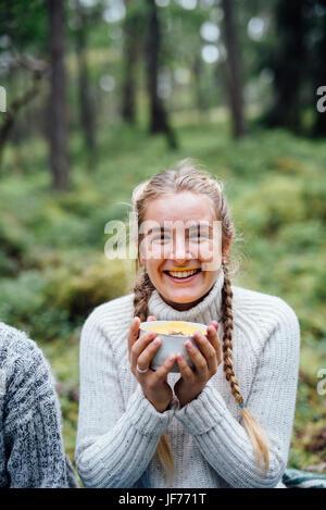 Eine Frau hält eine Schüssel mit Suppe Stockbild