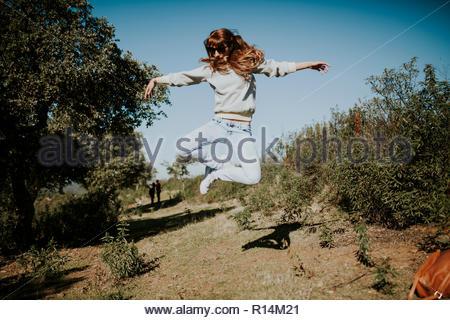 Eine junge Frau, springen in die Luft, umgeben von Pflanzen Stockbild