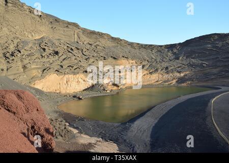Grüne Lagune und Wind erodiert vulkanischer Asche und Lava Klippen, El Golfo, Lanzarote, Kanarische Inseln, Februar. Stockbild