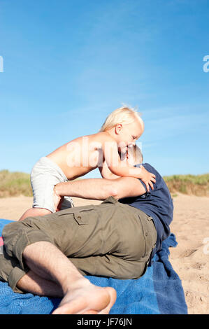 Vater mit Sohn am Strand spielen Stockbild
