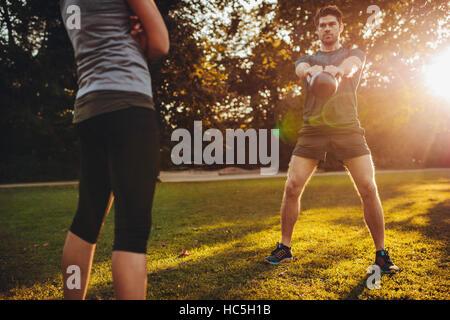 Junger Mann dabei Kettlebell-Gewicht-Training mit weiblichen Personaltrainer im Park. Fit Mann geschwungen Wasserkocher Stockbild