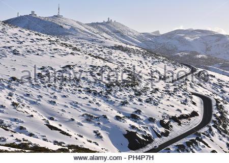 TF-24 Straße durch vulkanische Landschaft von Teide Nationalpark bedeckt mit Schnee, Teneriffa, Kanarische Inseln, Spanien. Sternwarte im Hintergrund. Stockbild