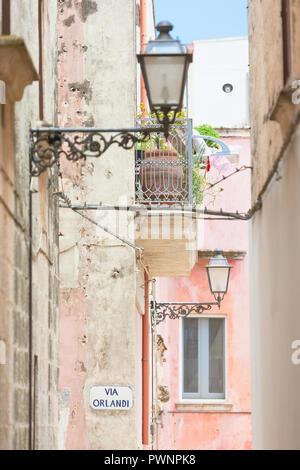 Specchia, Apulien, Italien - Laternen und einen Balkon in einer historischen Gasse Stockbild