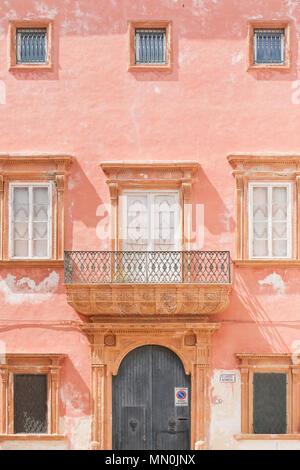 Gallipoli, Apulien, Italien - ein rosa Fassade mit einem scheunentor und mehrere Fenster Stockbild