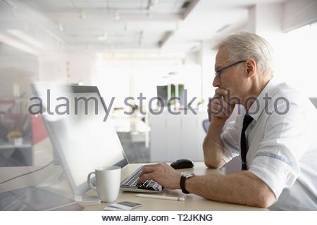 Fokussierte Geschäftsmann mit Computer im Büro Stockbild
