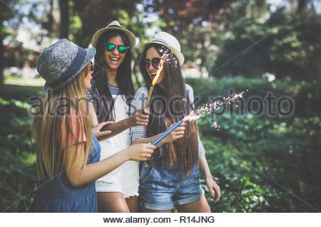 Drei junge Frauen tragen Sonnenbrillen holding Wunderkerzen Stockbild