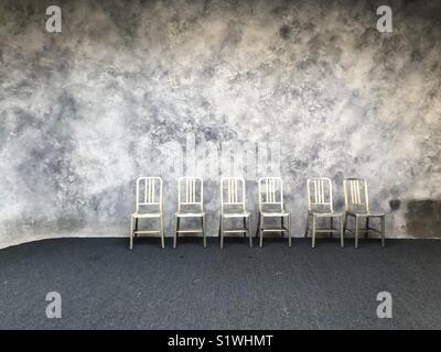 Stühle aufgereiht im leeren Zimmer Stockbild