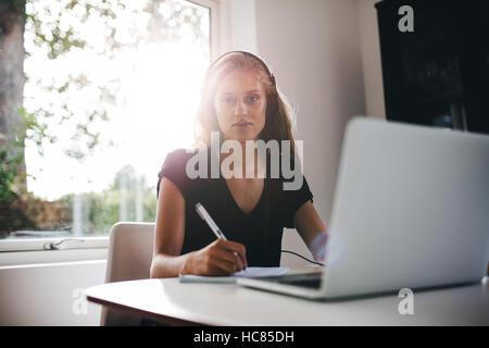 Portrait von junge Frau sitzt in Küche mit Kopfhörern Anmerkung zu schreiben. Frau mit Laptop zu Hause Stockbild
