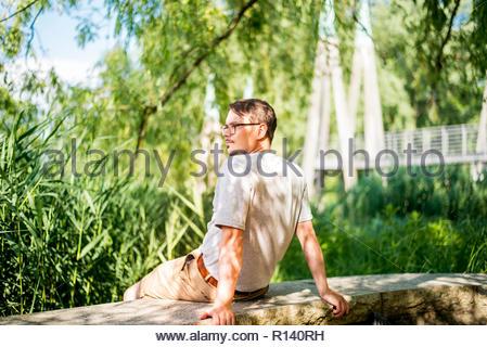 Ansicht von hinten von einem Mann, der durch Bäume Stockbild