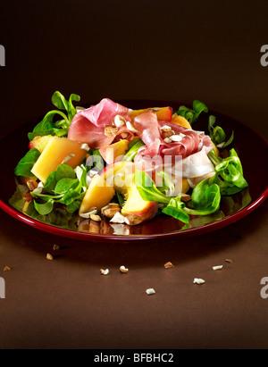Pfirsich und Melone Salat mit Parmaschinken (Prosciutto), Mandeln und Feldsalat. Stockbild