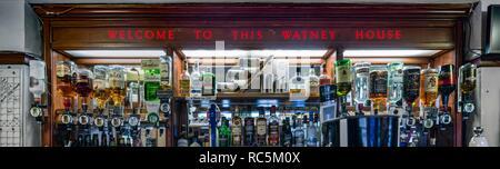 Die Königin Elizabeth, Merrow Street, Walworth, Southwark, London, 2017. Detail der öffentlichen Haus Lytham Street Bar, zeigt die Zähler mit Geist Flaschen, Optik und eine beleuchtete Werbeschild für die ehemalige Brauerei Watneys hinter sich. Stockbild