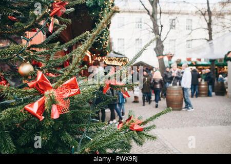 Weihnachtsbaum oder Tannenzweigen im Vordergrund. Der Weihnachtsmarkt in Deutschland ist unscharf im Hintergrund. Ferienhäuser. Die Menschen in den Ferien entspannen. Stockbild