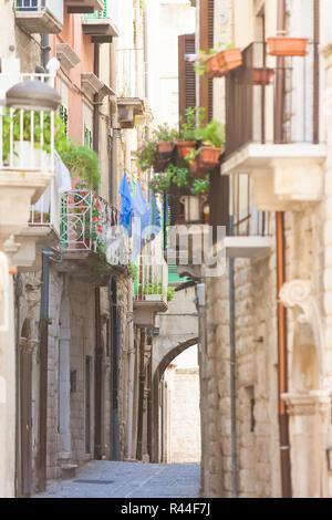 Molfetta, Apulien, Italien - alte Balkone und einen historischen Torbogen in einer Gasse von Molfetta Stockbild