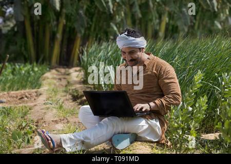 Happy Farmer oder Dorf Mann Betrieb einen Laptop Computer in seiner Landwirtschaft. Stockbild