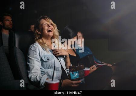 Gruppe von Freunden sitzen im multiplex-Kino und Film Komödie. Junge Menschen Film in Kino und lachen. Stockbild