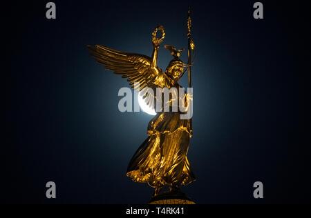 Berlin, Deutschland. 18 Apr, 2019. Scheint der Mond hinter der Statue von Victoria ('Goldelse') auf der Siegessäule. Credit: Paul Zinken/dpa/Alamy leben Nachrichten Stockbild
