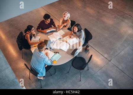 Draufsicht der Gruppe von Studenten, die zusammen am Tisch sitzen. Studenten Gruppe Studie und lächelnd. Stockbild