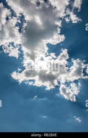 Weiße Wolken im blauen Himmel und die Sonne Stockbild