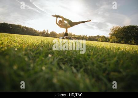 Passen Sie junges Paar Acroyoga auf Rasen zu tun. Mann und Frau im Park paar Yoga-Übungen praktizieren. Stockbild
