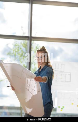 Frau betrachten Pläne durch die Glaswand Stockbild