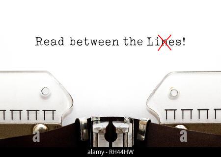 Text gelesen zwischen den liegt auf alten Schreibmaschine. Die in der Regel verwendeten Wort in der ursprünglichen Idiom Linien liegt geändert wird. Stockbild