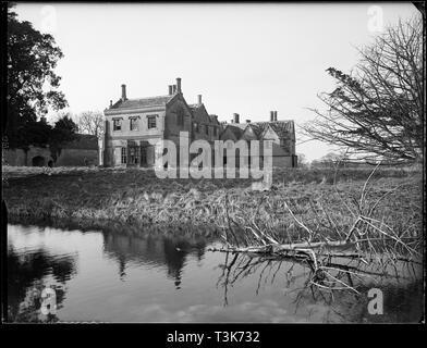 Scrivelsby Court, Scrivelsby, Lincolnshire, 1956. Ein Blick auf das verlassene Haus von den L-förmigen Graben im Süden. Das Gebäude, die auf diesem Foto abgebildet ist, wurde in c 1956-1959 abgerissen, nachdem zuvor durch einen Brand zerstört worden. Das heutige Gebäude auf dem Gelände, auch als Scrivelsby Gericht bekannt, ursprünglich das torhaus war an das Haupthaus. Der umliegende Park wurde von humphry Repton im Jahre 1791 gelegt. Stockbild