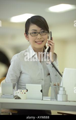 Frau am Telefon im Büro Stockbild