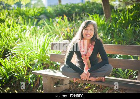 Japanische Frau sitzt auf der Parkbank Stockbild