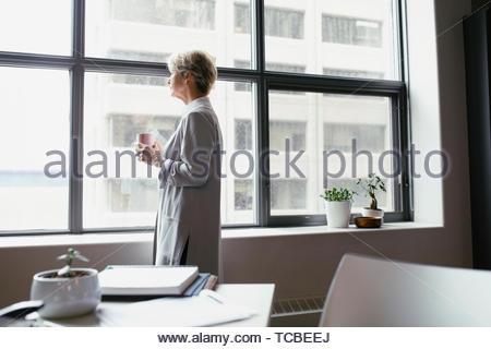 Nachdenklich Geschäftsfrau trinken Kaffee im Büro Stockbild