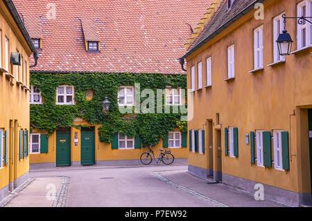 Fuggerei, Augsburg, Bayern, Deutschland - Blick durch eine der Gassen mit den armenhäusern. Stockbild