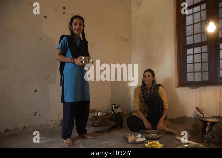 Gerne ländliche Frau sitzt in der Küche Kochen auf Brennholz auf dem Boden, während ihre Schule Tochter steht mit einem Tiffin. Stockbild