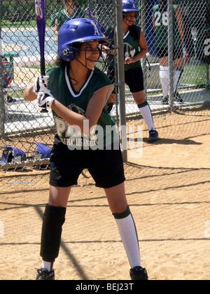 Mädchen in uniform spielen softball Stockbild