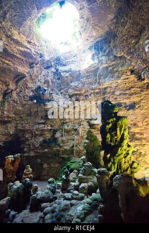 Grotta di Castellano, Apulien, Italien - beeindruckende Steinformationen durch ein Loch leuchtet Stockbild