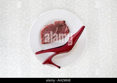 rote high-Heel mit Fleisch auf weißen Teller, Studio gedreht Stockbild